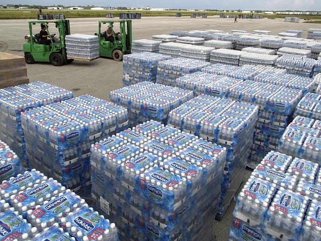 vysokozdvižné vozíky překládají zboží na paletách, konkrétně plastové láhve s vodou